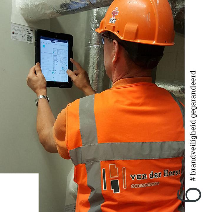 Man in oranje kleding voert technische inspectie uit